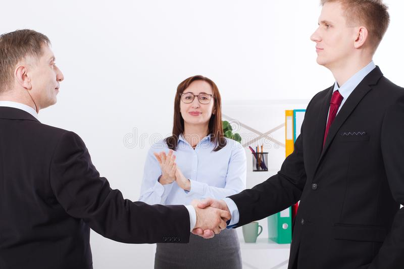 Conceito bem sucedido da parceria do negócio com aperto de mão dos businessmans Aplauso feliz da mulher de negócios no fundo do e imagens de stock royalty free