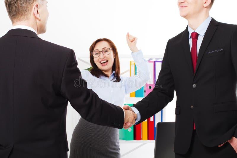 Conceito bem sucedido da parceria do negócio com aperto de mão dos businessmans Mulher de negócios feliz no fundo do escritório T fotografia de stock royalty free