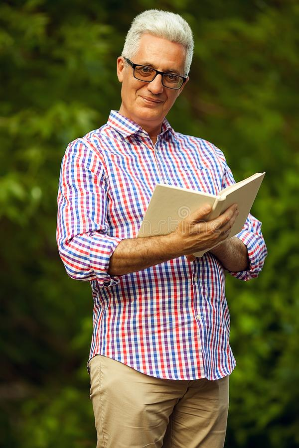 Conceito bem sucedido do homem Retrato de um homem maduro de sorriso com livro fotografia de stock royalty free