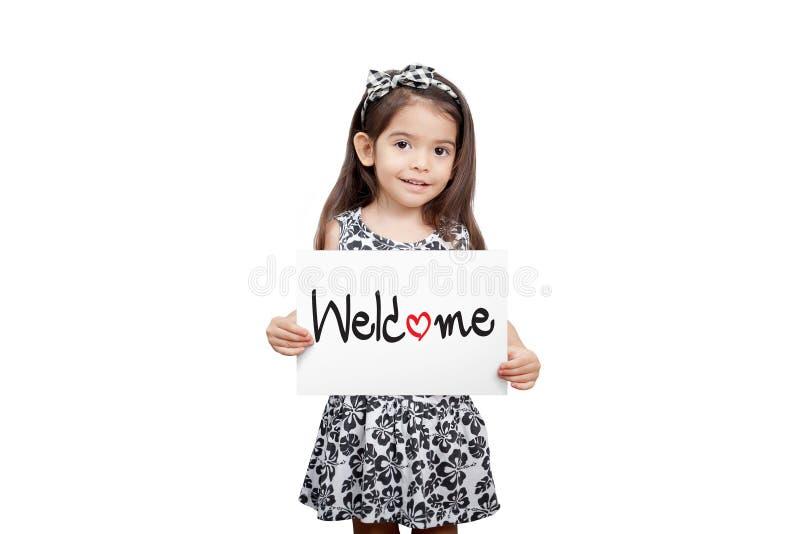 Conceito bem-vindo do negócio, menina bonito que guarda um suporte do sinal bem-vindo imagens de stock