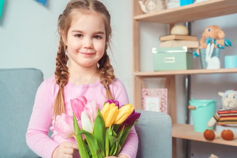 Conceito bonito pequeno da celebração do dia do ` s da mãe da menina em casa que guarda o ramalhete das flores imagem de stock royalty free