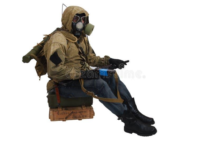 conceito Cargo-apocalíptico da ficção - assediador na máscara de gás com a caixa da arma e da munição Texto na caixa no russo - t foto de stock