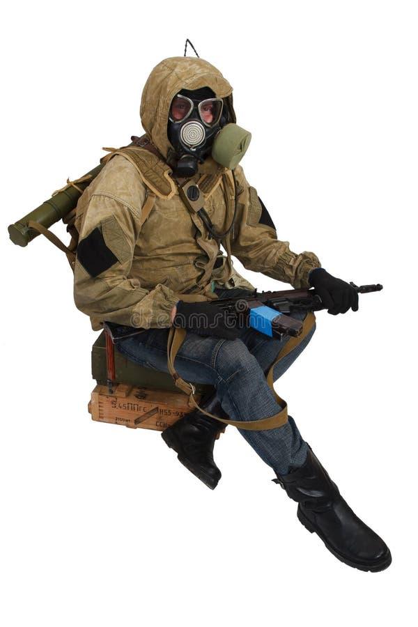 conceito Cargo-apocalíptico da ficção - assediador na máscara de gás com a caixa da arma e da munição Texto na caixa no russo - t fotos de stock