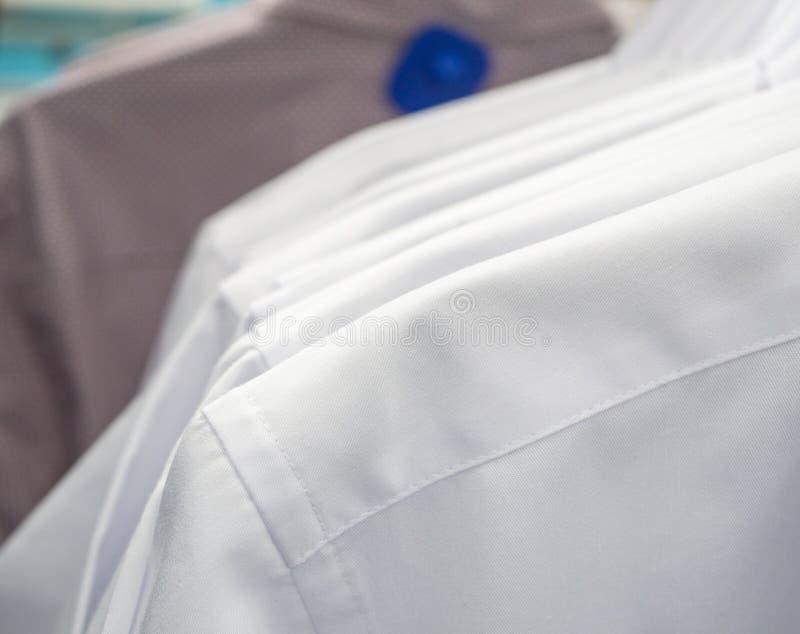 Conceito clássico das camisas do negócio Camisas dos homens em ganchos, fim acima fotografia de stock royalty free