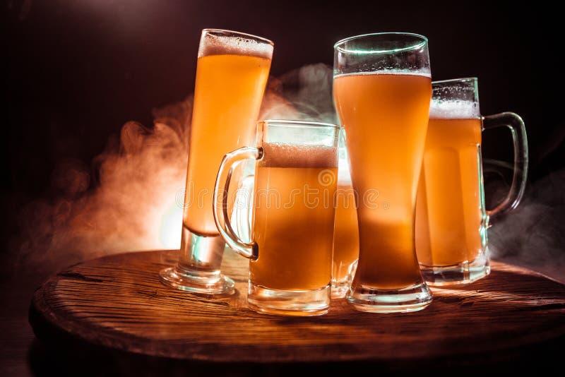 Conceito creativo Vidros de cerveja na tabela de madeira no fundo nevoento tonificado escuro fotografia de stock royalty free