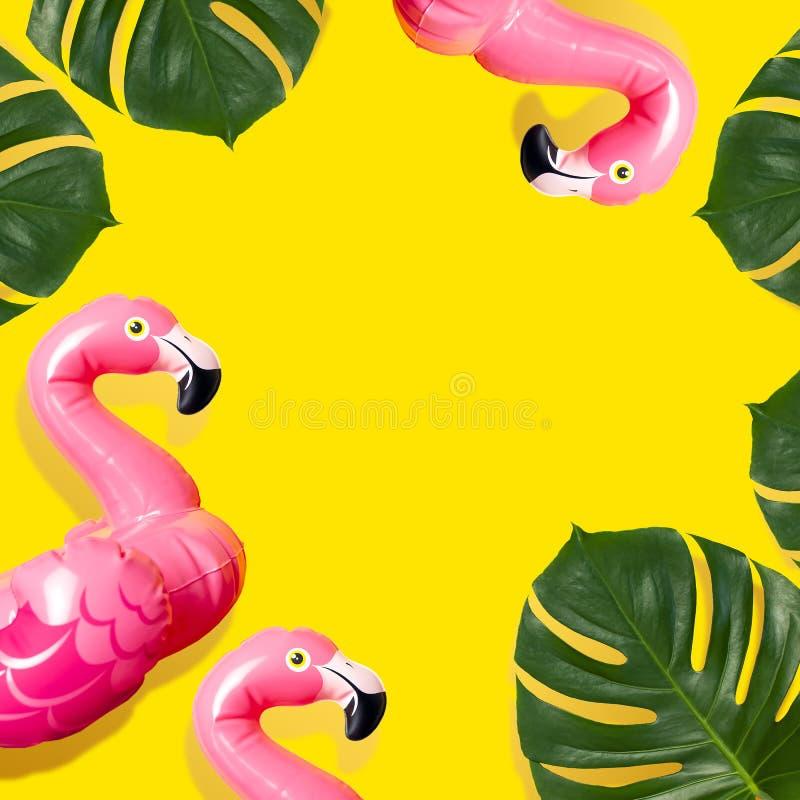 Conceito criativo da praia do verão Mini flamingo cor-de-rosa inflável e monstera tropical da folha no fundo amarelo, partido do  imagem de stock royalty free