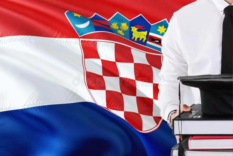 Conceito croata bem sucedido da educação do estudante Guardando livros e tampão da graduação sobre o fundo da bandeira da Croácia fotografia de stock royalty free