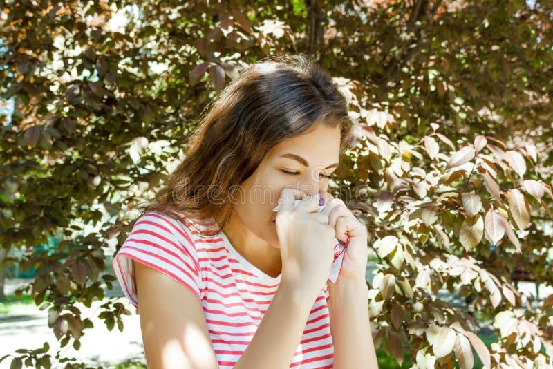 Conceito da alergia Espirrando a moça com o limpador do nariz entre árvores de florescência no parque imagem de stock