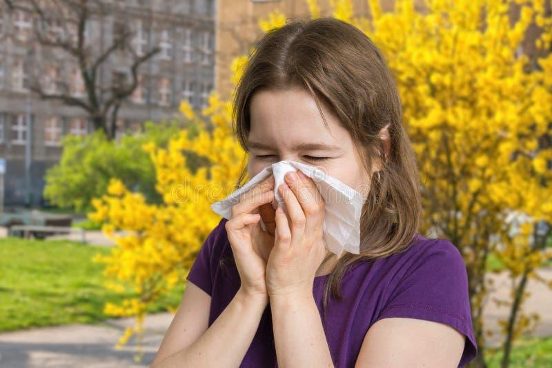 Conceito da alergia A mulher alérgica nova é espirrando e de sopro seu nariz foto de stock royalty free