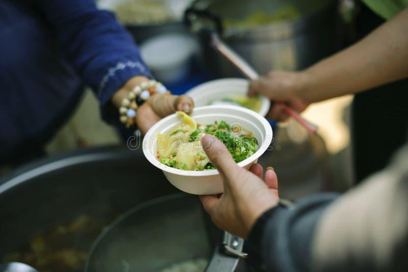 Conceito da alimentação: Os voluntários dão o alimento aos pobres: doar o alimento está ajudando amigos humanos na sociedade: Pov imagem de stock