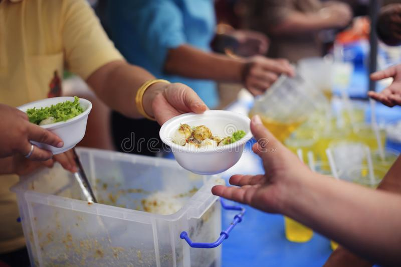 Conceito da alimentação: Os voluntários dão o alimento aos pobres: doar o alimento está ajudando amigos humanos na sociedade: Pov imagem de stock royalty free