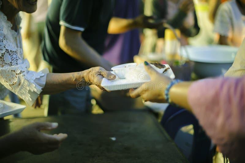 Conceito da alimentação: Os voluntários dão o alimento aos pobres: doar o alimento está ajudando amigos humanos na sociedade: Pov fotos de stock
