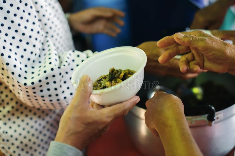 Conceito da alimentação: Os voluntários dão o alimento aos pobres: doar o alimento está ajudando amigos humanos na sociedade: Pov imagens de stock royalty free