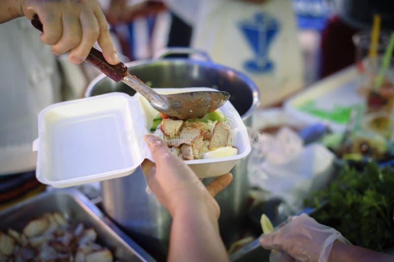 Conceito da alimentação: Os voluntários dão o alimento aos pobres: doar o alimento está ajudando amigos humanos na sociedade: Pov fotografia de stock