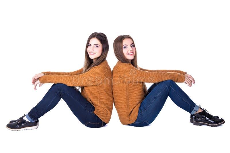 Conceito da amizade - retrato de um assento de duas meninas isolado em w fotos de stock