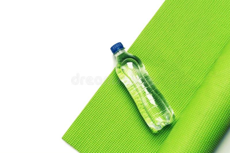 Conceito da aptidão - esteira da ioga e garrafa verdes da água fotos de stock royalty free