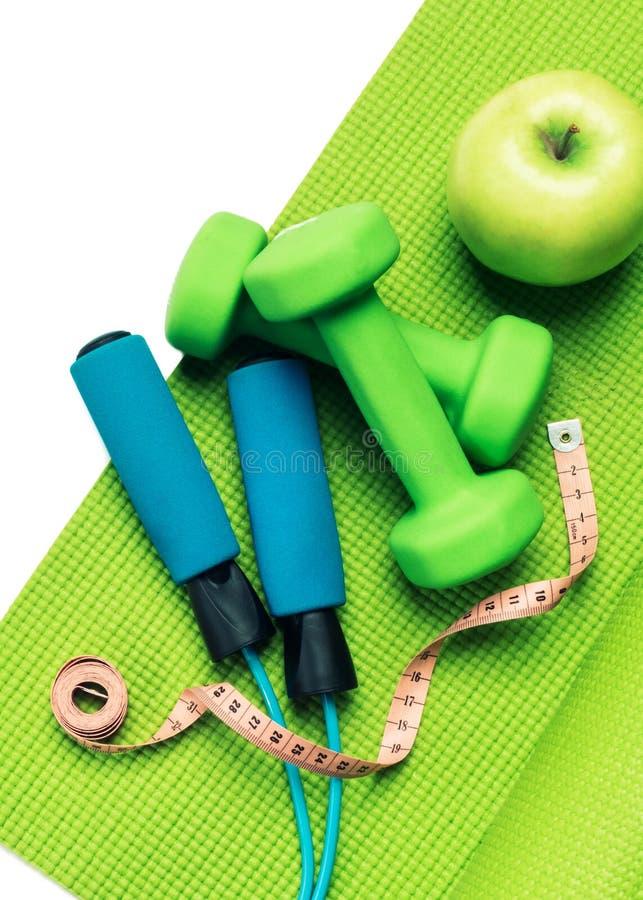 Conceito da aptidão - esteira da ioga, maçã, pesos e corda de salto fotografia de stock