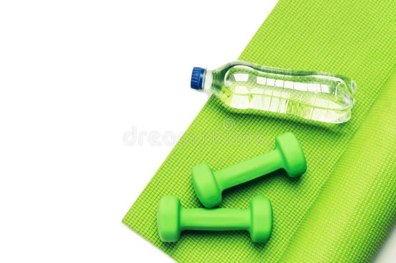Conceito da aptidão - esteira e pesos verdes da ioga foto de stock royalty free