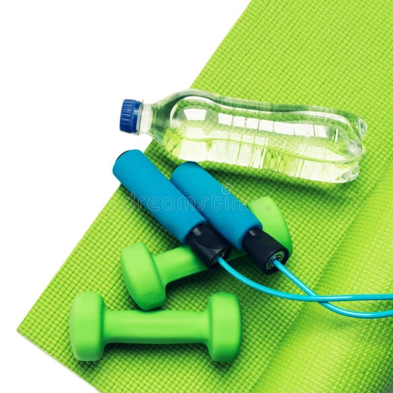 Conceito da aptidão - esteira, pesos e garrafa verdes da ioga imagens de stock