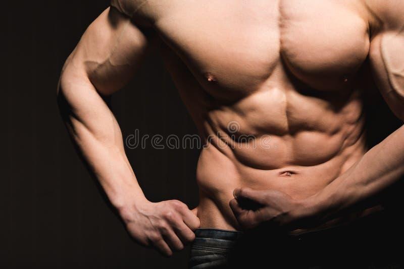 Conceito da aptidão Torso muscular e apto do homem novo que tem o pão masculino perfeito do Abs, do bíceps e da caixa com corpo a fotografia de stock