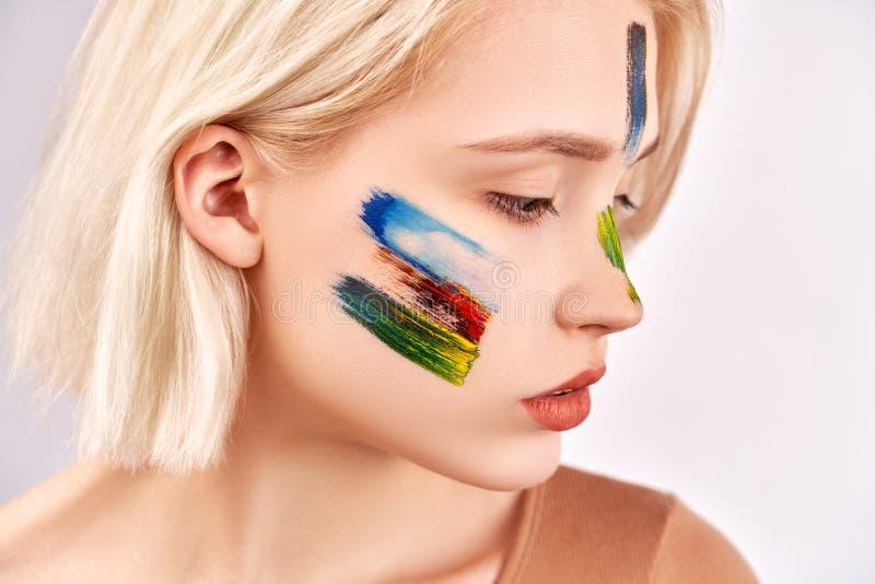 Conceito da arte da cara A mulher agradável com composição bonita da arte, tem o cabelo louro curto, poses contra o fundo branco foto de stock