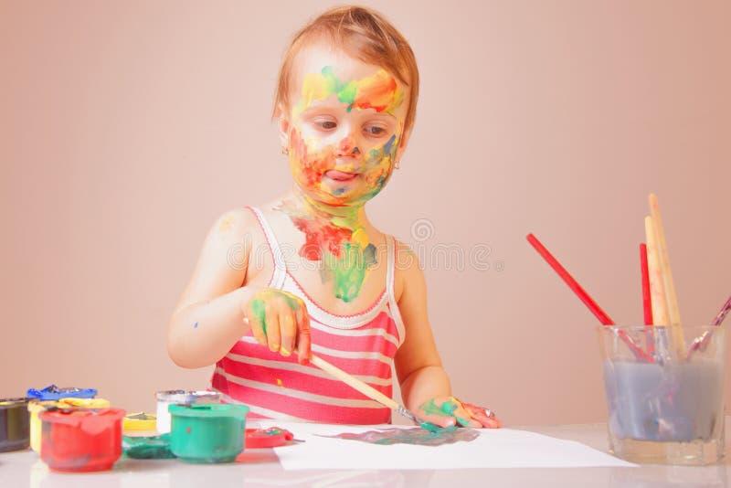Conceito da arte, o criativo e da felicidade da infância Mãos e cara pintadas coloridas em uma moça bonita imagem de stock royalty free