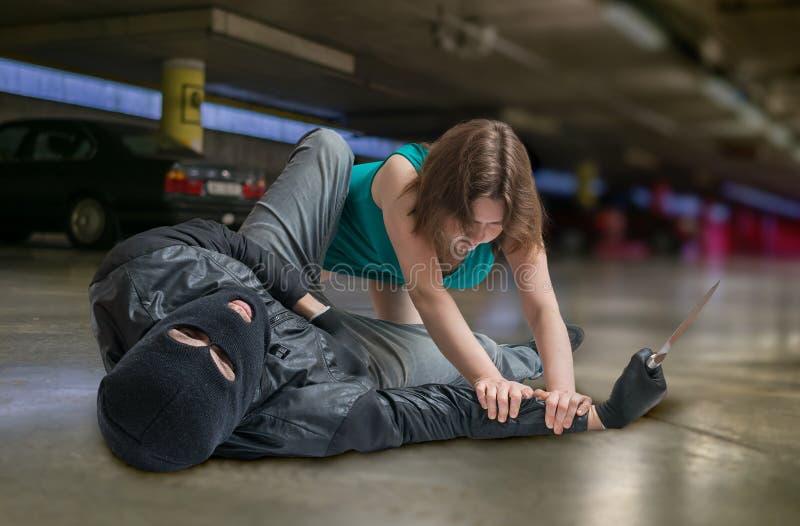 Conceito da autodefesa A jovem mulher está lutando com ladrão ou ladrão fotografia de stock royalty free