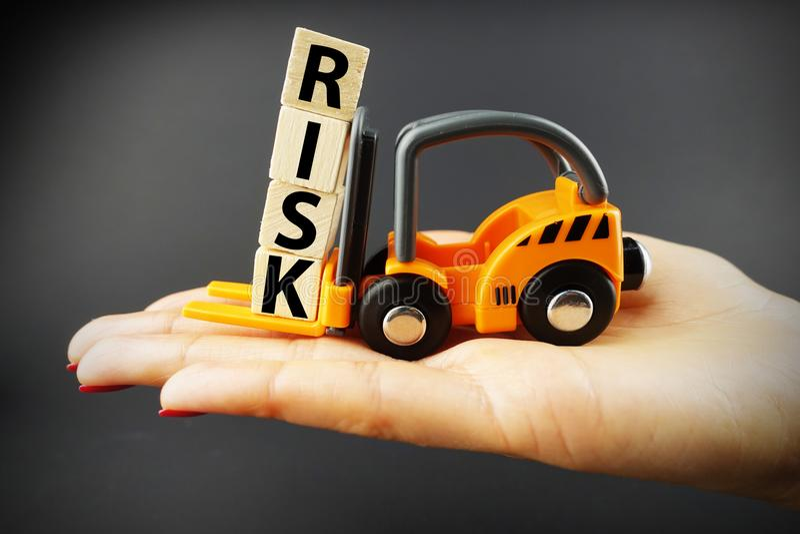 Conceito da avaliação de riscos sugerido pela empilhadeira alaranjada que opera blocos de madeira fotografia de stock royalty free