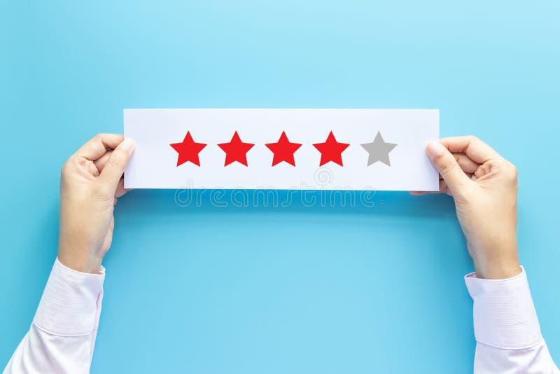 Conceito da avalia??o e do feedback o cliente que guarda o papel com revisão satisfeita dá perto a estrela para a experiência do  fotografia de stock