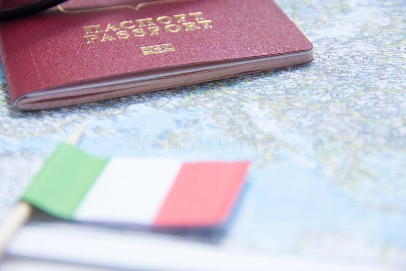 Conceito da aventura Óculos de sol, bandeira pequena de Itália e passaporte no mapa imagem de stock royalty free