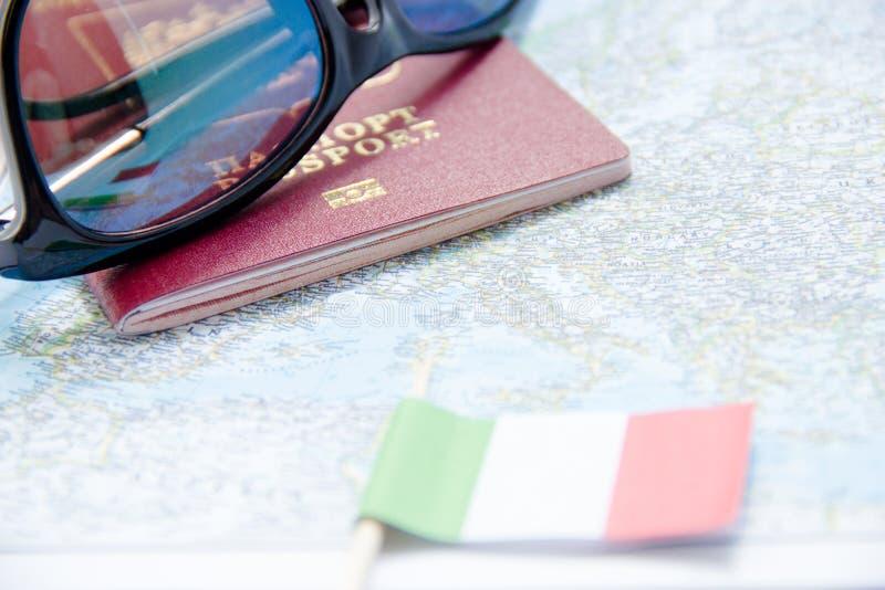 Conceito da aventura Óculos de sol, bandeira pequena de Itália e passaporte no mapa imagem de stock