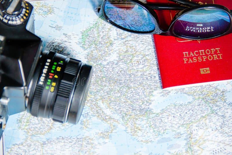 Conceito da aventura Óculos de sol, câmera preta retro e passaporte no mapa fotografia de stock