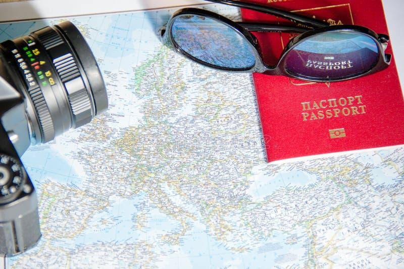 Conceito da aventura Óculos de sol, câmera preta retro e passaporte no mapa imagem de stock royalty free
