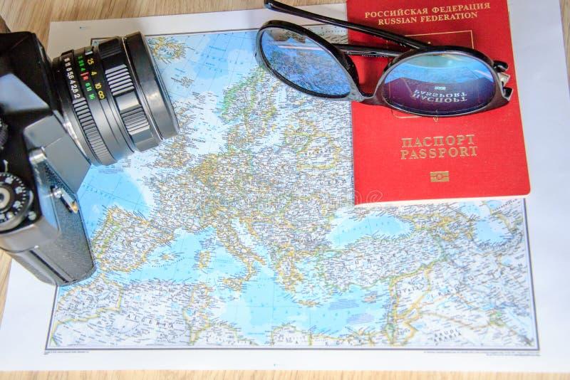 Conceito da aventura Óculos de sol, câmera preta retro e passaporte no mapa fotografia de stock royalty free