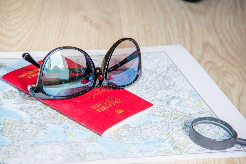 Conceito da aventura Óculos de sol e passaportes no mapa fotos de stock royalty free