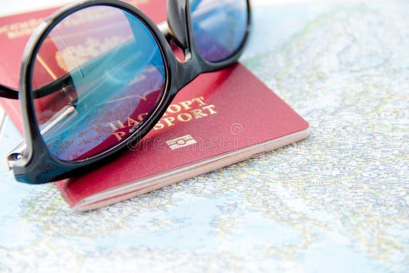 Conceito da aventura Óculos de sol e passaportes no mapa foto de stock royalty free