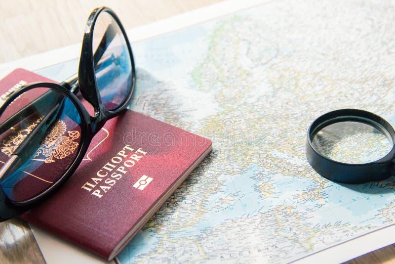 Conceito da aventura Óculos de sol, lupa e passaporte estrangeiro no mapa fotos de stock