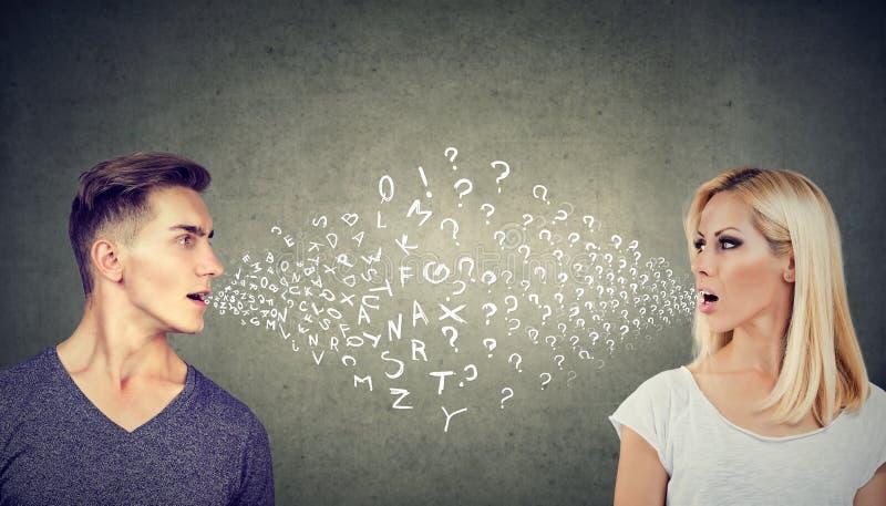 Conceito da barreira linguística Homem considerável que fala a uma mulher atrativa com muitas perguntas foto de stock