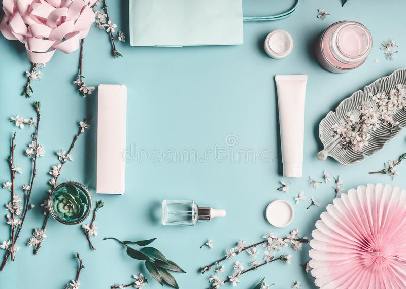 Conceito da beleza com os produtos, o saco de compras e os galhos cosméticos faciais com a flor de cerejeira no desktop azul past imagens de stock