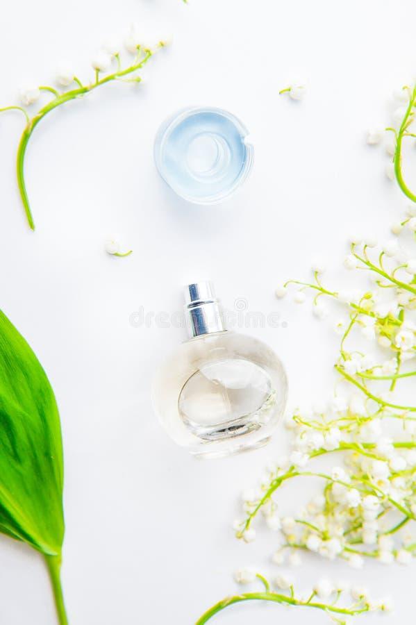 Conceito da beleza Configuração lisa com a garrafa de perfume esférica cercada por lírios frescos do vale, das flores do poder-lí fotografia de stock