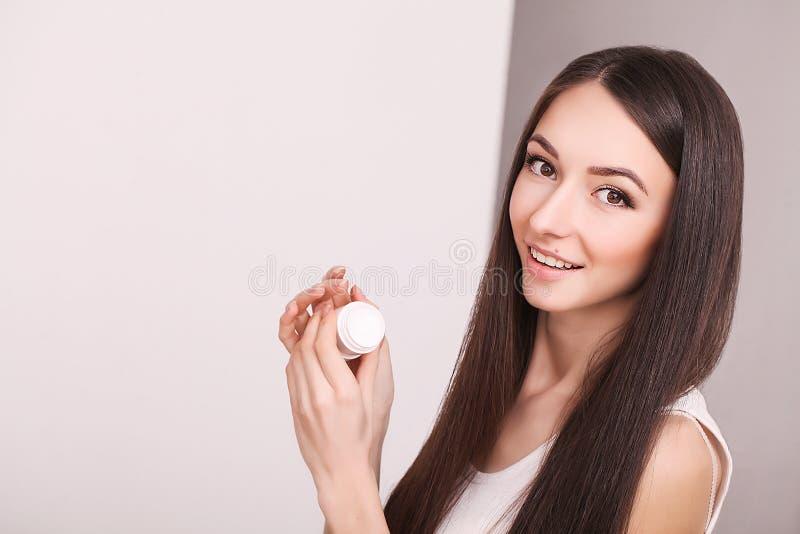 Conceito da beleza, dos povos, do skincare e dos cosméticos - jovem mulher feliz com creme hidratando disponível e facial fotografia de stock