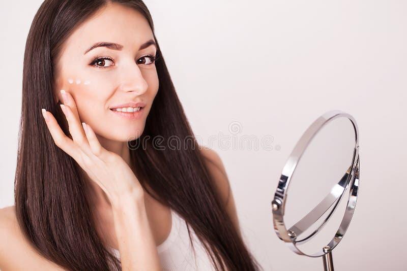 Conceito da beleza, dos povos, dos cosméticos, do skincare e da saúde - jovem mulher de sorriso feliz que aplica o creme a sua ca foto de stock royalty free