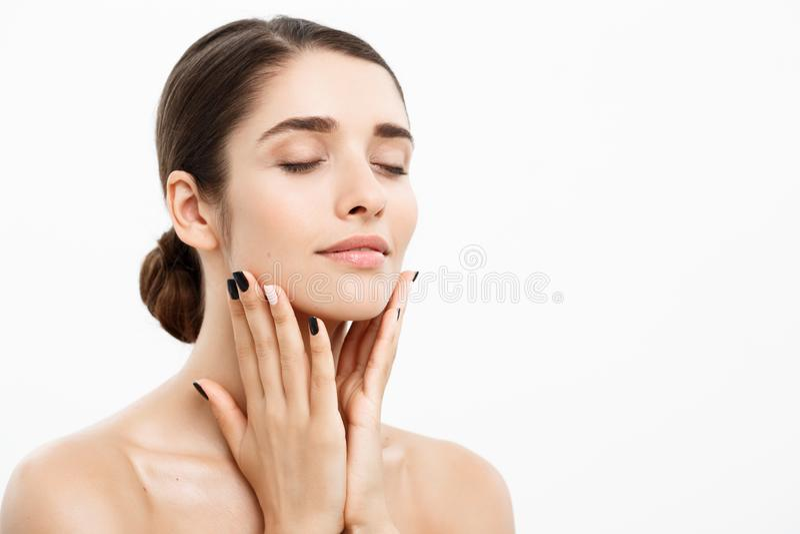 Conceito da beleza e dos cuidados com a pele - jovem mulher bonita ascendente próxima que toca em sua pele no fundo branco imagem de stock