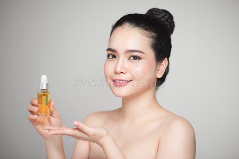 Conceito da beleza Mulher bonita asiática com a pele perfeita que guarda o óleo foto de stock royalty free