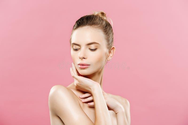 Conceito da beleza - mulher bonita com fim fresco limpo da pele acima no estúdio cor-de-rosa Menina saudável da pele Face cosmeto imagem de stock