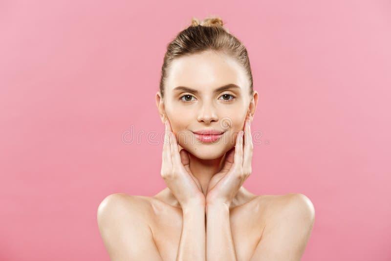 Conceito da beleza - mulher bonita com fim fresco limpo da pele acima no estúdio cor-de-rosa Menina saudável da pele Face cosmeto foto de stock royalty free