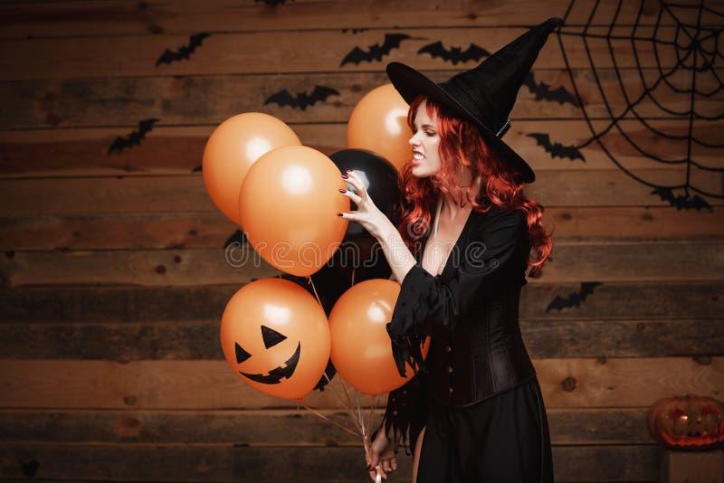 Conceito da bruxa de Dia das Bruxas - a mulher caucasiano bonita na bruxa traja a comemoração de Dia das Bruxas que levanta com l fotografia de stock