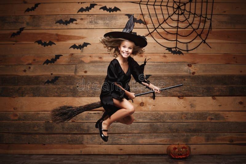 Conceito da bruxa de Dia das Bruxas - voo caucasiano pequeno da criança da bruxa no cabo de vassoura mágico sobre o fundo da Web  foto de stock