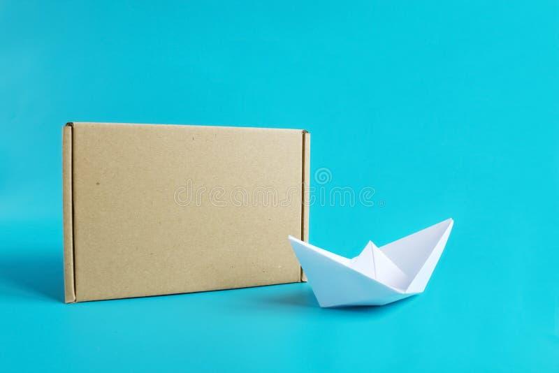 Conceito da carga de transporte Navio de papel perto da caixa do of?cio isolada no fundo azul Copie o espa?o imagem de stock