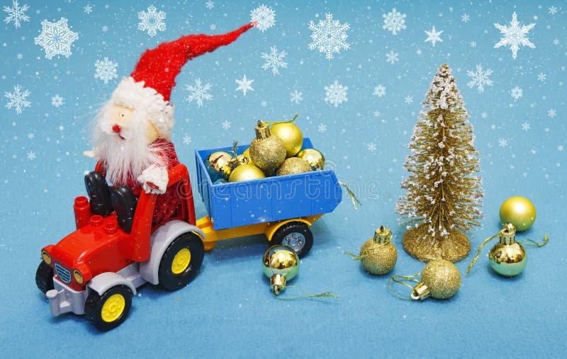 Conceito da celebração do feriado do Natal Santa Claus que leva bolas do Xmas no trator com reboque foto de stock royalty free